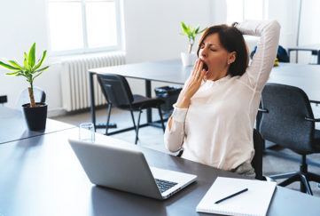 Young businesswoman yawning in front of laptop