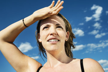Woman sweating against a blue sky