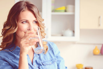 Blonde woman in blue blouse drinking glass of water in kitchen