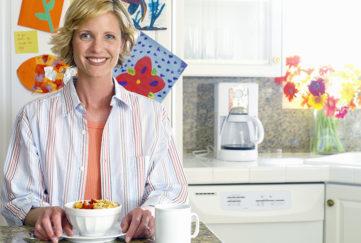 Woman eating breakfast alone in kitchen, peaceful