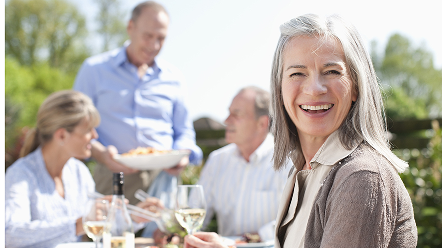 Portrait of smiling woman drinking wine at patio table with friends