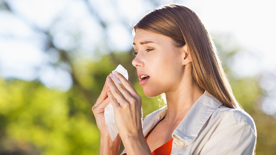 Beautiful woman using tissue while sneezing