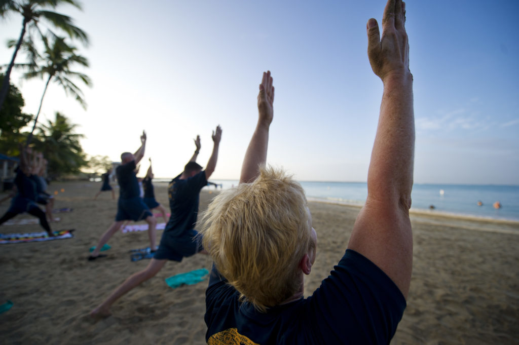 People practising yoga on a beach