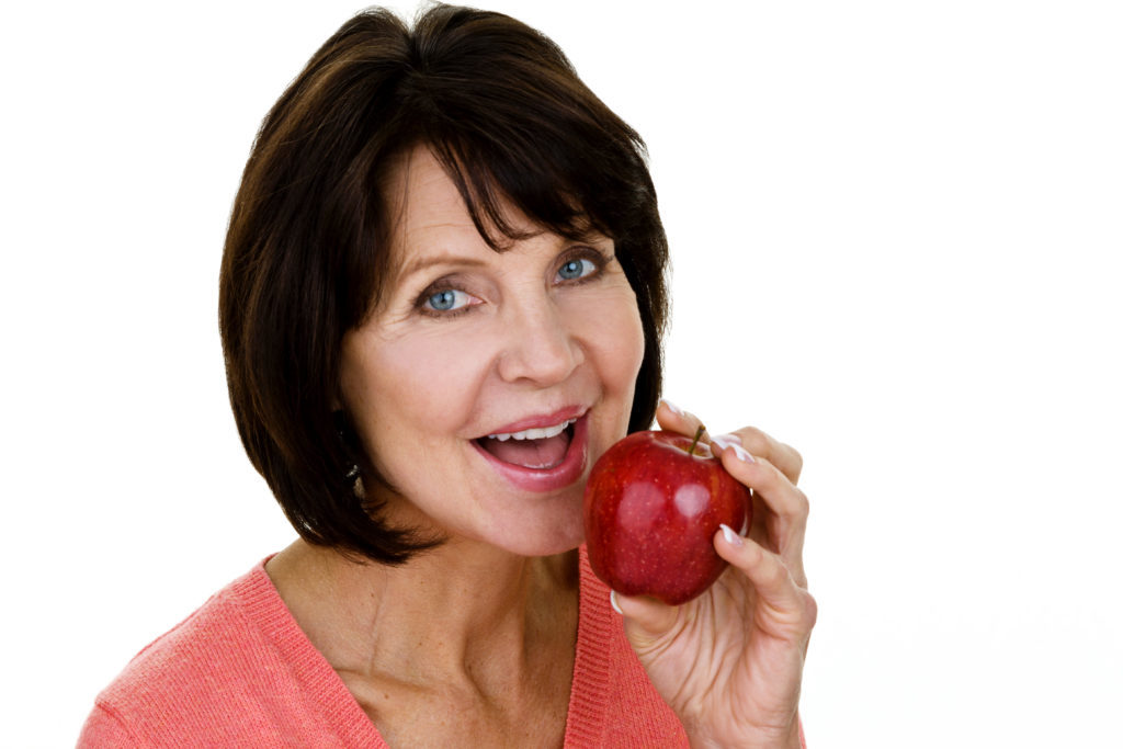 Beautiful mature woman eating an apple while being isolated on white background