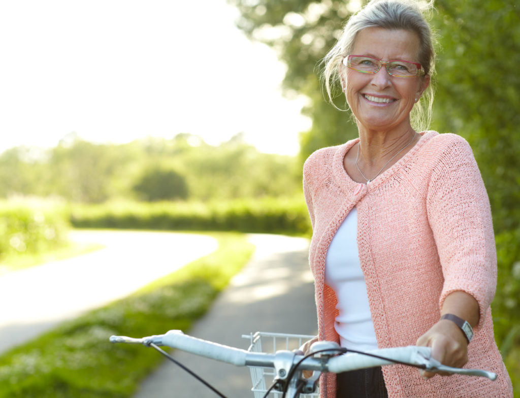 Smiling senior woman standing on a country lane with her bicycle
