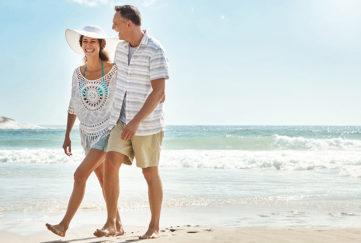 Shot of a mature couple walking along the beach
