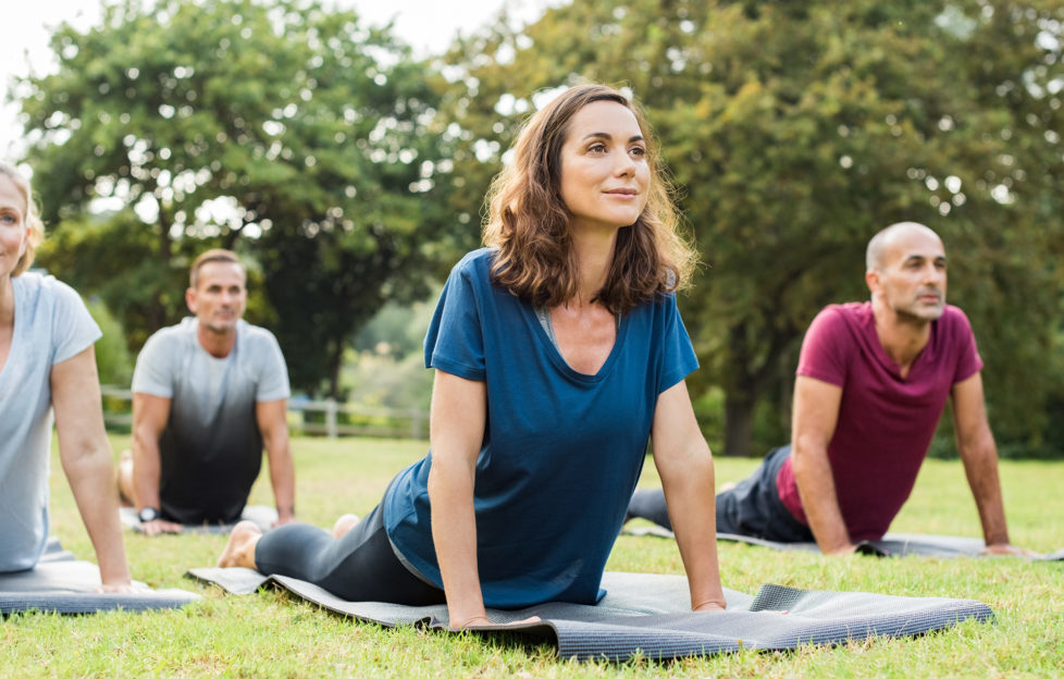 """Mature healthy people doing yoga at park. Group of multiethnic people exercising on green grass with yoga mat. Happy men and smiling women in yoga class doing exercise outdoor.""""r"""