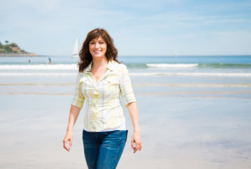 woman walking along the shore on the beach