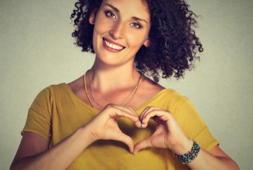 Woman with jaw-length curly dark hair and mustard jumper, smiling, maj=king heart shape with her hands