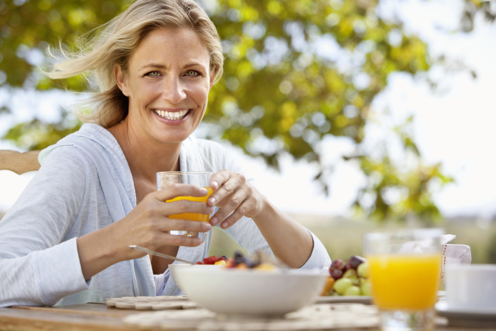 Smiling mature woman with orange juice at breakfast table outdoors - summertime hygge