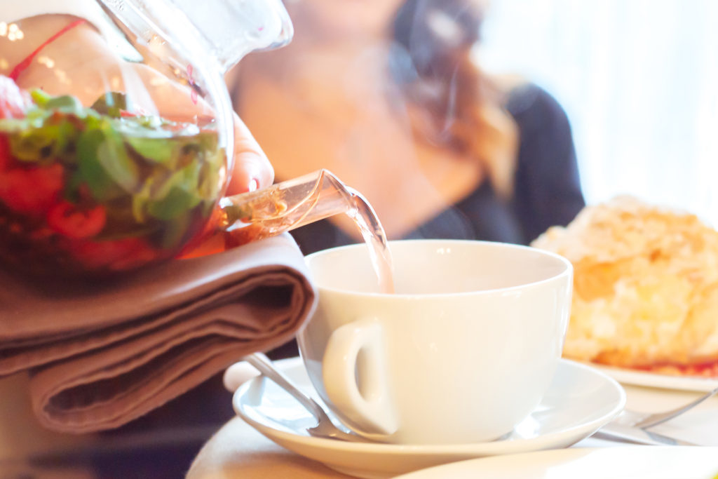 The waiter poured a fresh herbal tea in elegant white porcelain cups. Glass teapot, transparent. teai mint with strawberries. In the background, visiting the restaurant in a shallow  DOF