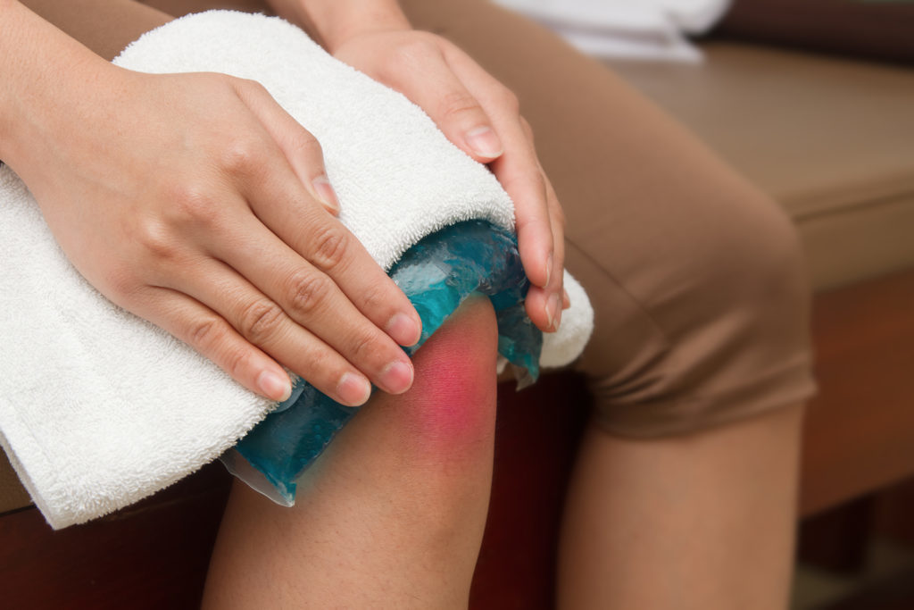 woman applying cold pack on  swollen hurting knee