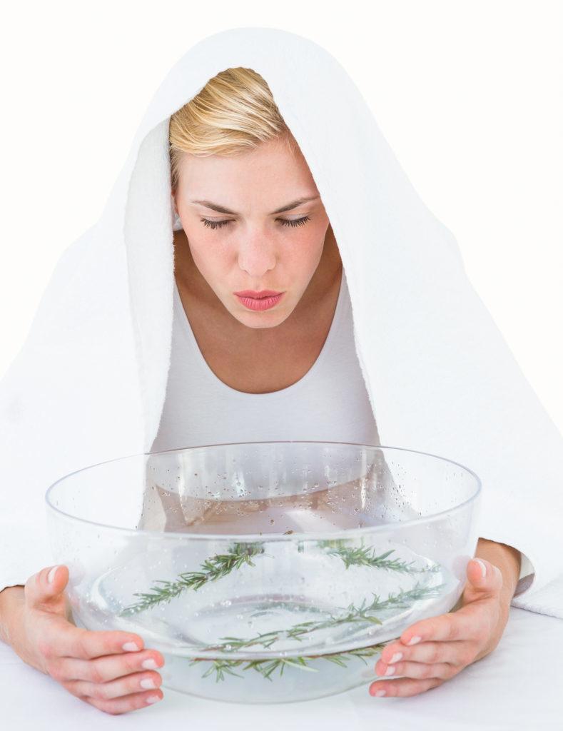 Blonde woman inhaling herbal medicine on white background