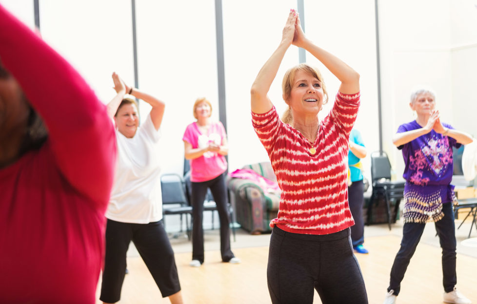 Women clap their hands over their heads as they learn new dance moves in thier local senior center. They are smiling and enjoying themselves.