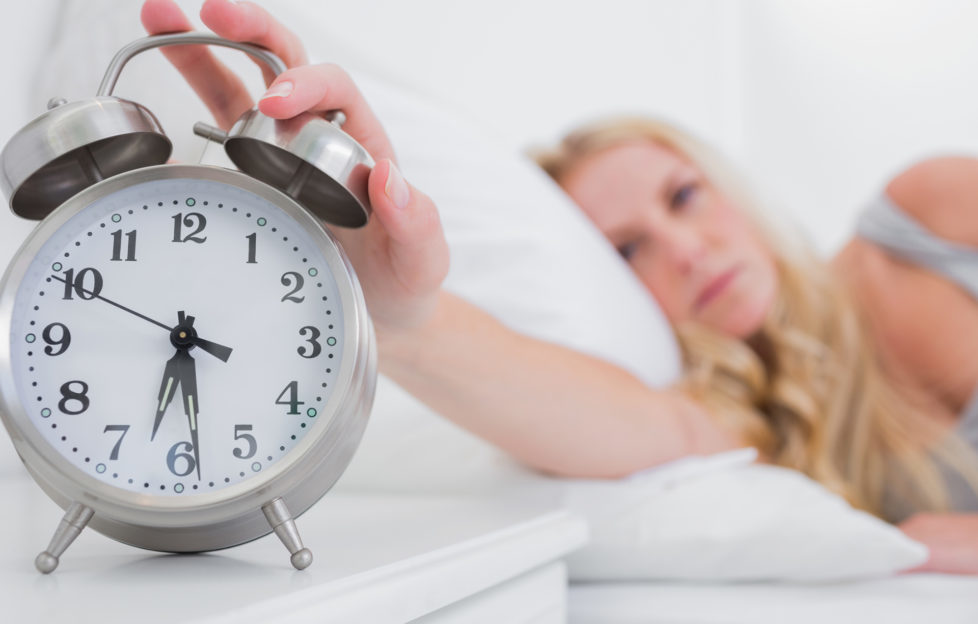Tired woman turning off the alarm clock in her bed