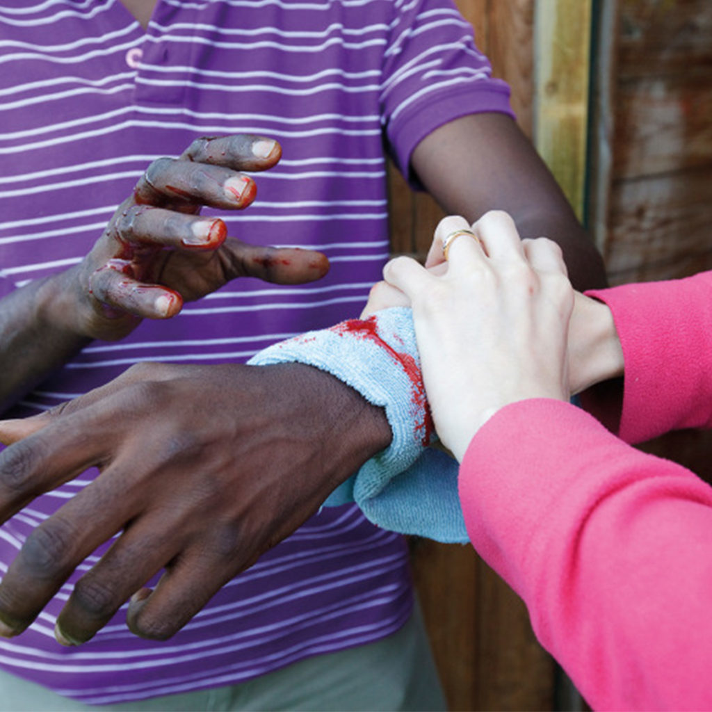 Man with bleeding arm, woman's hands firmly holding cloth over wound