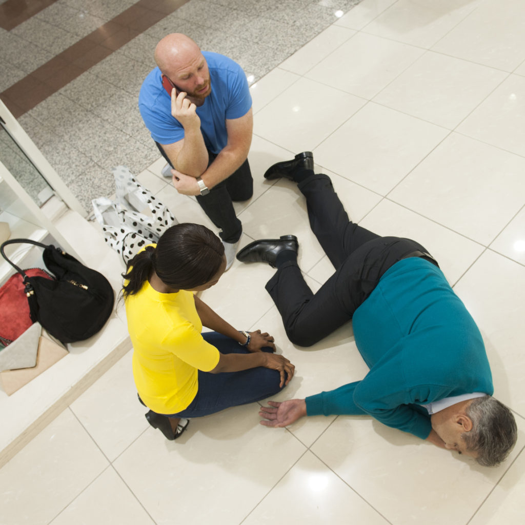 Man lying on side on shop floor, one knee bent, woman talking to him, another man phoning 999