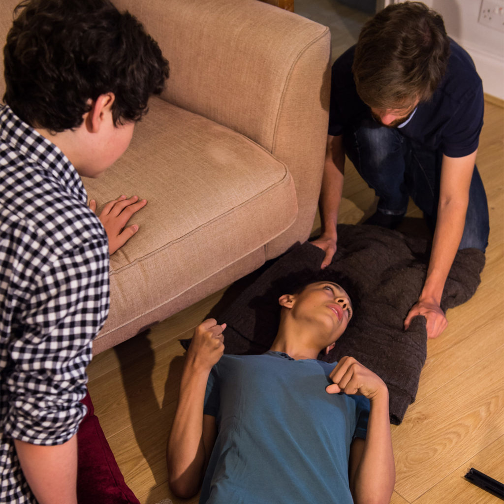 Young person lying on living room floor having seizyure, adult and a youth taking care of them