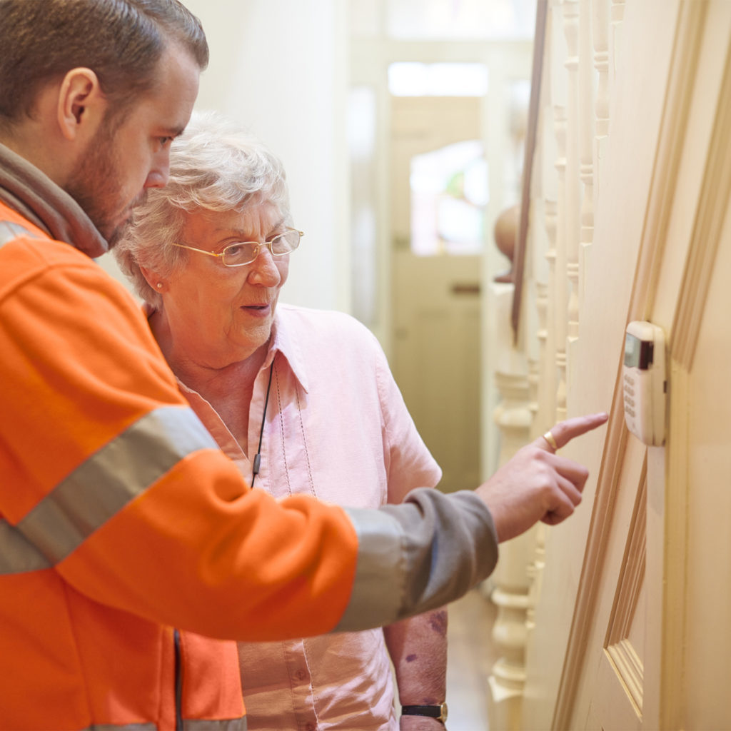 an alarm fitter demonstrates to a senior woman in her home how to set the home security system. The housing officer watches on to make sure her tenant is happy with the installation.