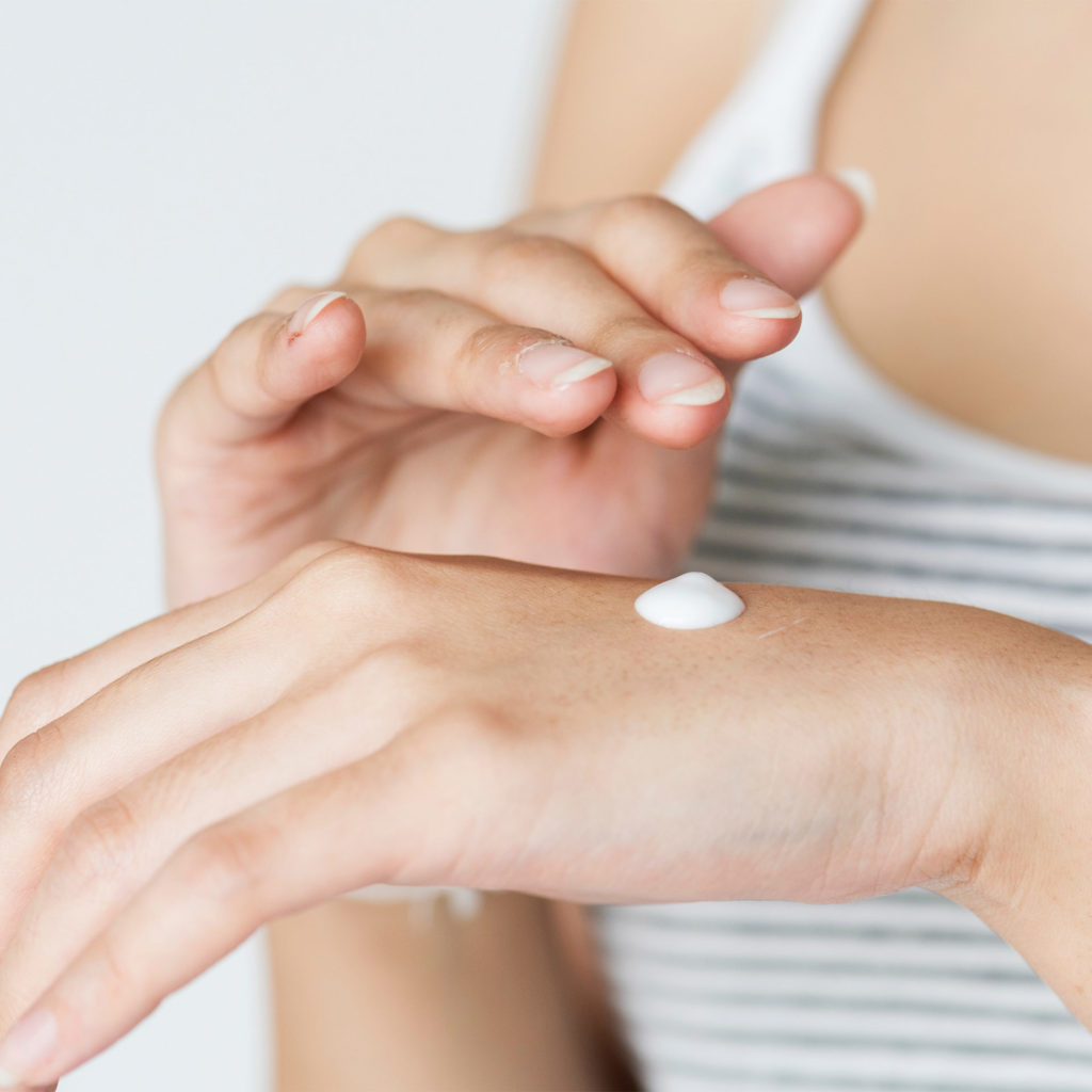 Woman applying cream to the back of her hand