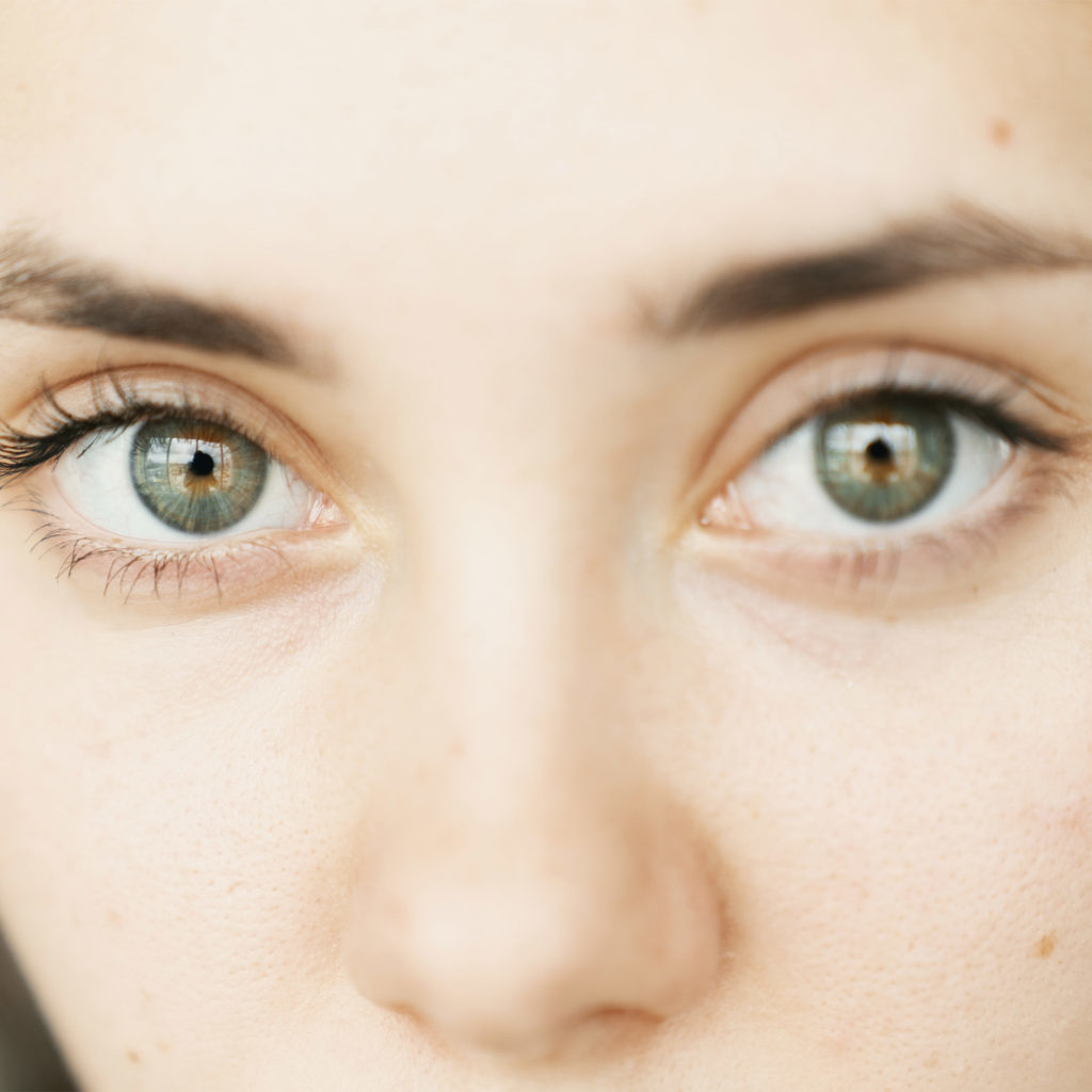 Close-up of young white woman's face, make-up free, green eyes, serious expression