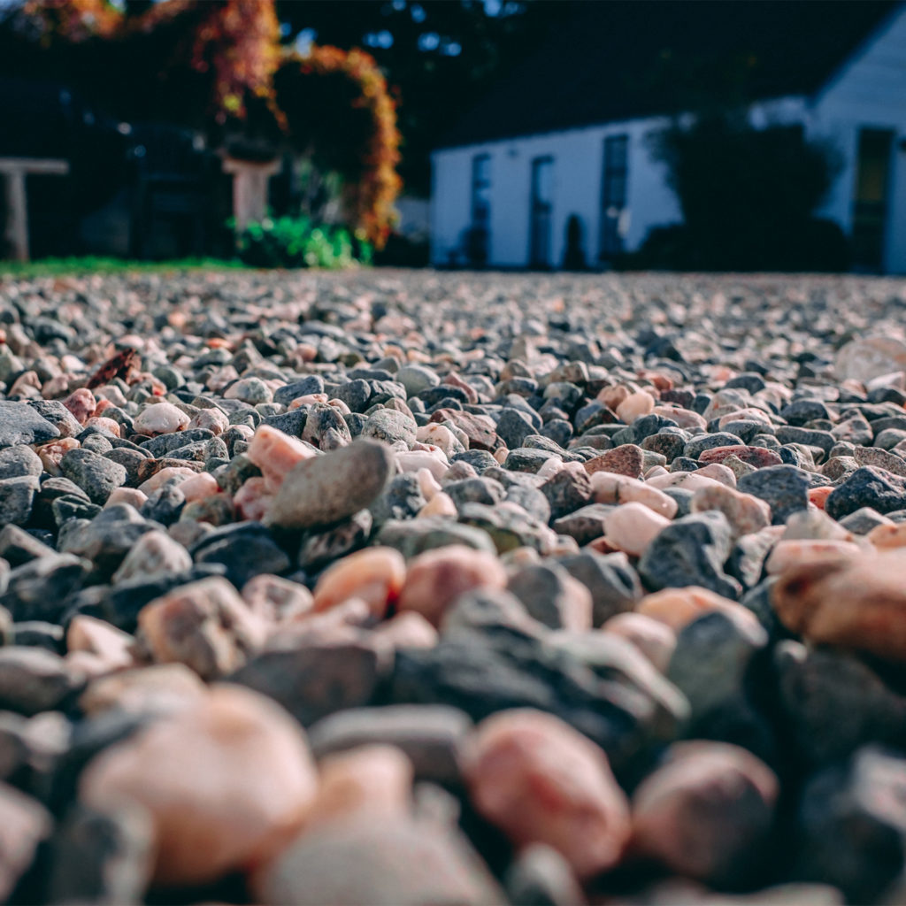 Gravel path close up with white painted cottage and bushes in the distance
