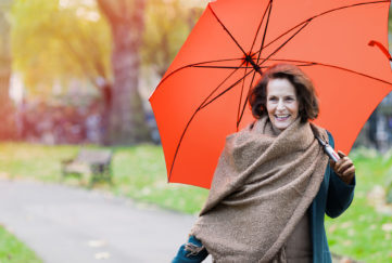 Walking senior woman in the park with umbrella