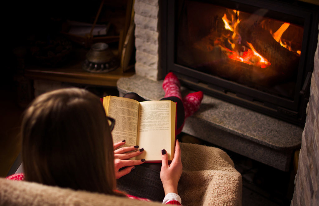 Female reading a book by the fireplace