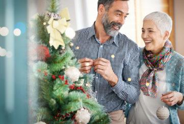 Senior couple decorating a Christmas tree.