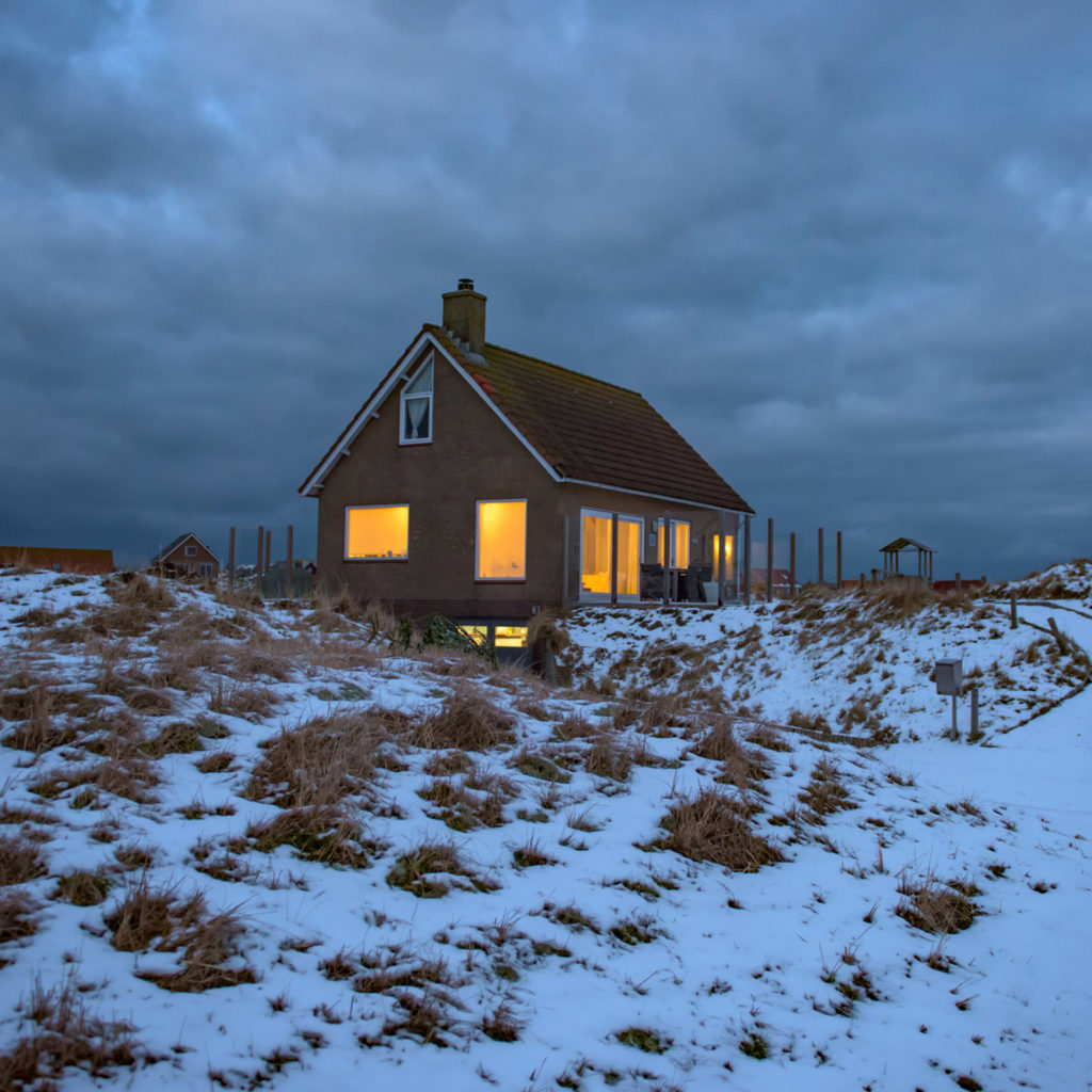 Isolated house on snowy hill with warm light from windows