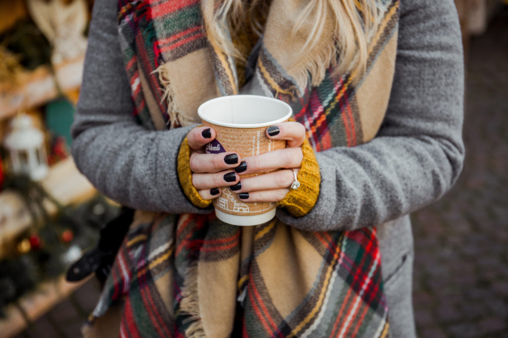 Woman's hands cupped around cardboard cup