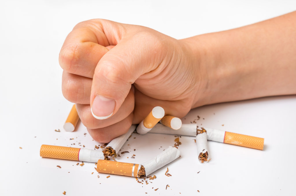 Human fist and pile of broken cigarettes - stop smoking concept