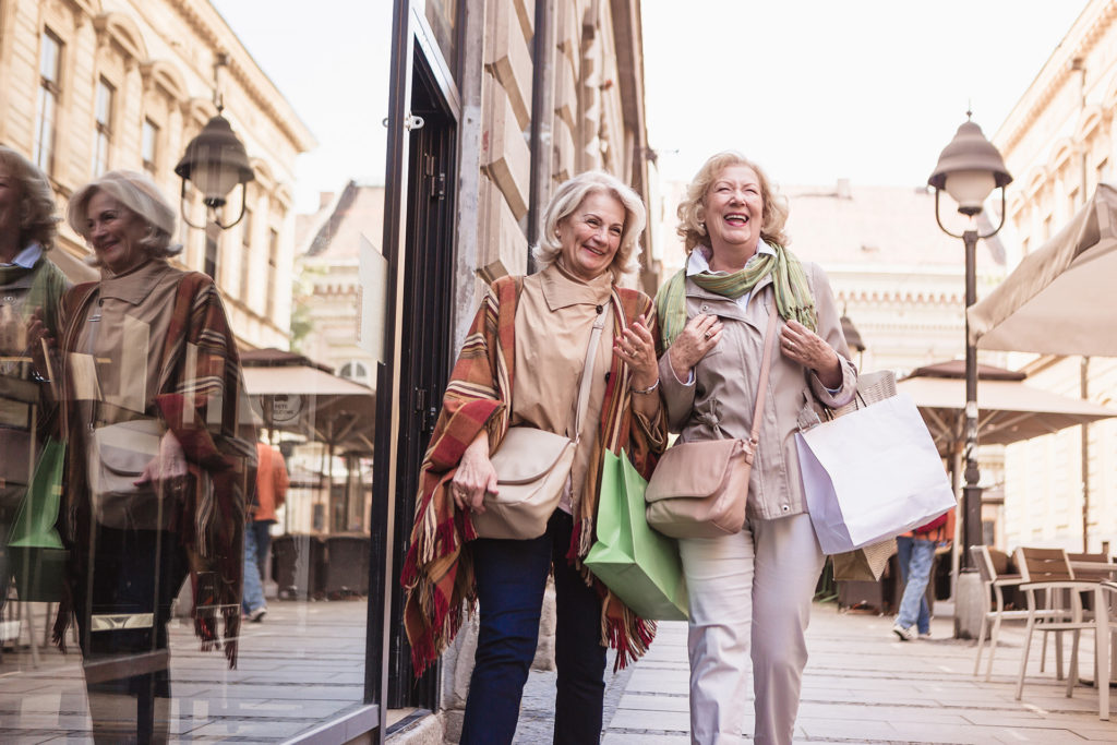 Two senior ladies in shopping. Talking, laughing carrying shopping bags.