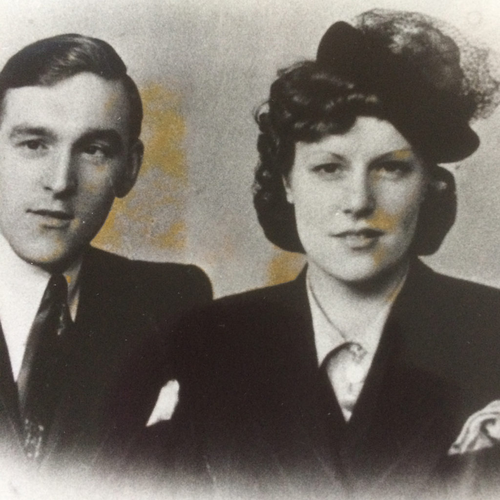 Black and white photo of WW2 wedding, bride wearing collared blouse, dark jacket and small dark hat decorated with net