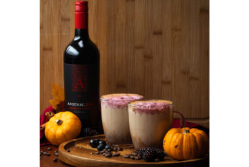Bottle of Apothic red wine, 2 cups of latte with red drizzle on top on round wooden board with miniature pumpkins and berries