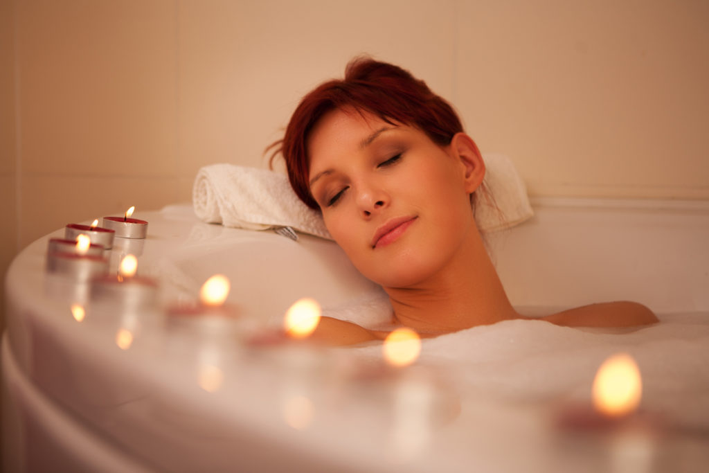 Woman relaxing in bath surrounded by tea lights