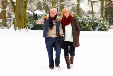 Image of elderly couple walking together in snow park on a winter day