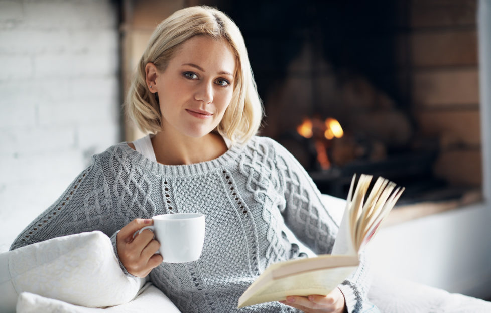 A young woman enjoying her novel with a hot drink while sitting inside near a fireplace Pic: Istockphoto