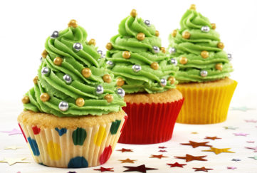 Three cupcakes with a tall swirl of green icing resembling Christmas trees, with sprinkles