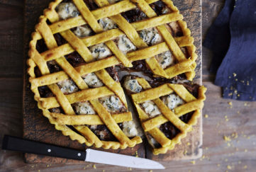 Lattice top cheese and onion pie with crumbled blue cheese and deep purple red onion visible underneath
