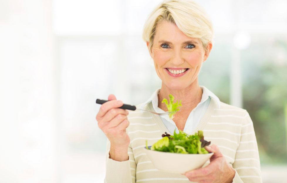 beautiful senior female vegetarian eating salad