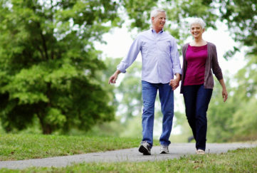 Senior couple walking in park on path with trees in the background.