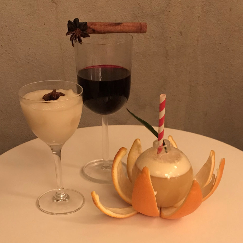 One glass of creamy apple, a glass of deep red mocktail garnished with a cinnamon stick, and a glass ball garnished with orange peel and a striped straw