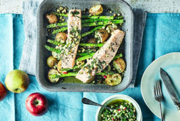 two pieces of baked salmon in a square dish strewn with asparagus and drizzled with salsa verde