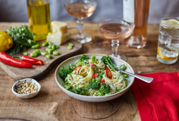 Bowl of spaghetti with creamy sauce and green broccoli, small dish of pine nuts on the side