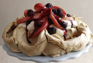 Golden brown meringue pavlova nest topped by red and purple cooked fruit