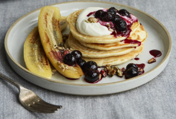 Small stack of pancakes on a plate with butter-fried bananas, lightly cooked blueberries and Greek yogurt