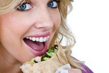 Woman eating a sandwich wrap