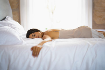 Woman lying face down hugging the mattress