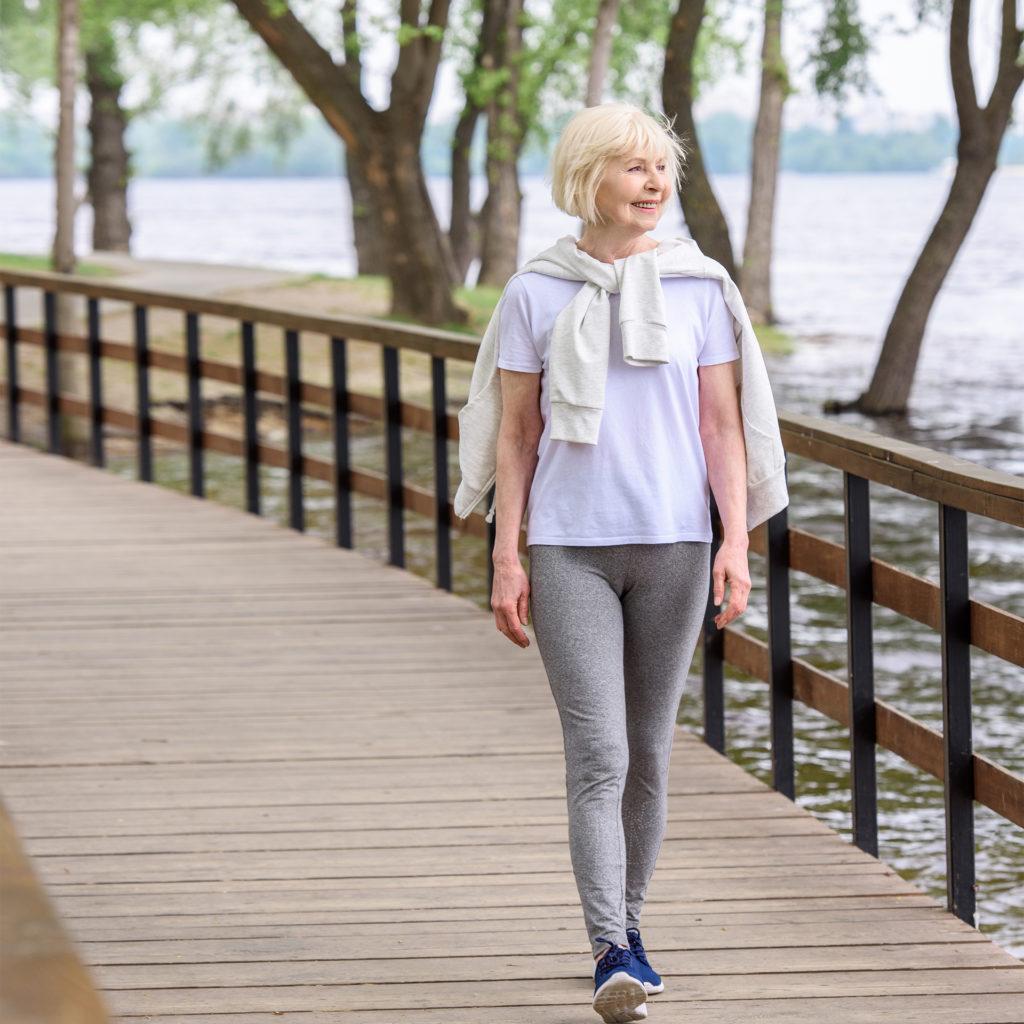 smiling senior woman walking on wooden boardwalk in park